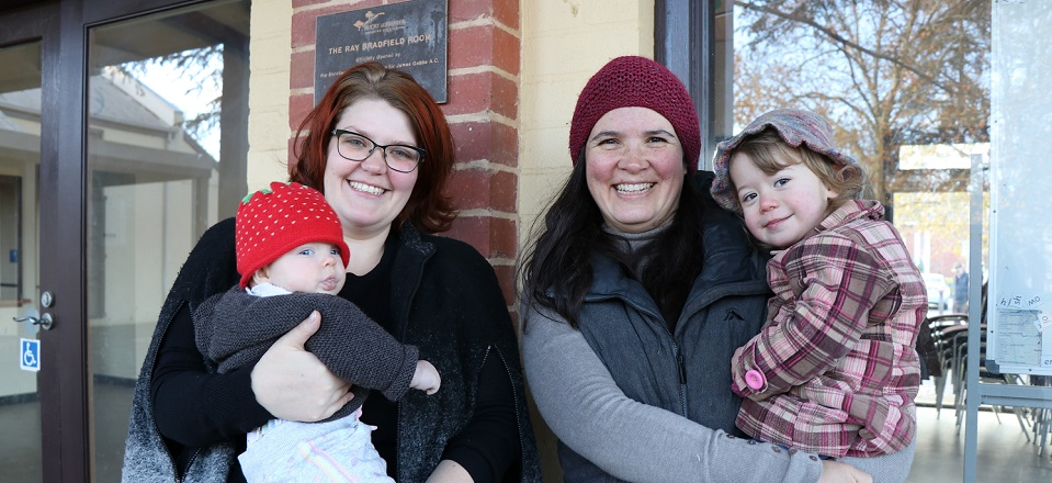 Two smiling mums with a baby and toddler.