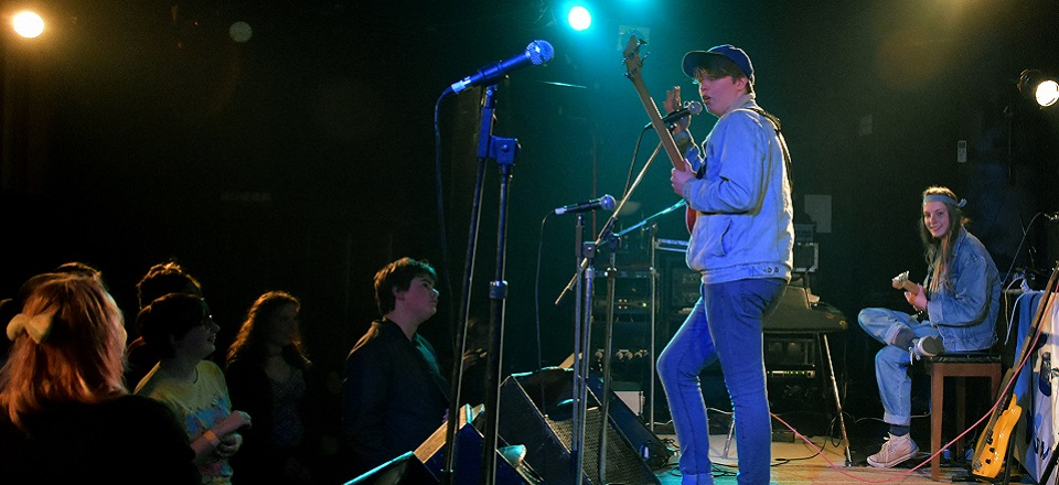 Two young musicians perform on stage.