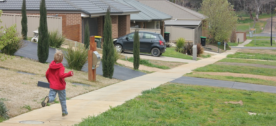 Image: Boy running in new housing estate in McKenzie Hill near Castlemaine.  Link to child page: Driveways and nature strips