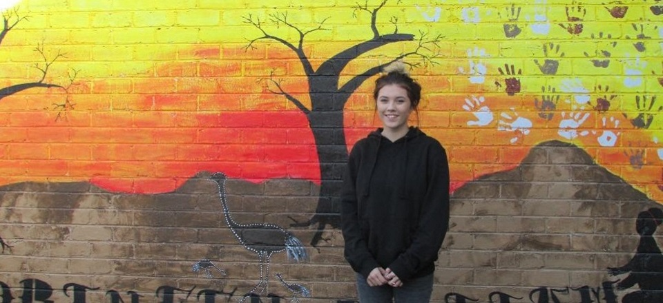 Image: Girl in front of mural  Link to child page: Youth grants