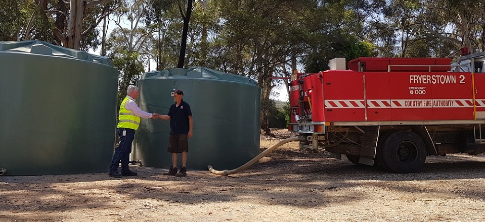 Council's Glenn Brown with Fryerstown CFA Captain Hamish MacCallum in front of the large water tanks.
