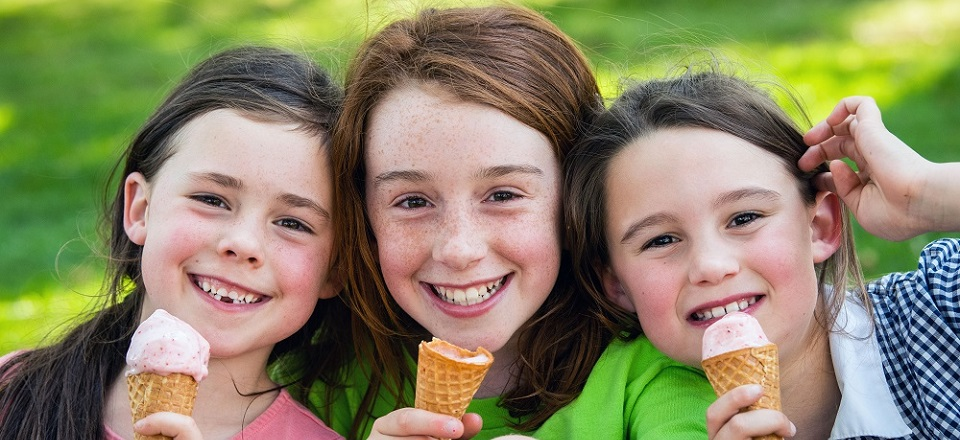 Three young girls eating ice cream.