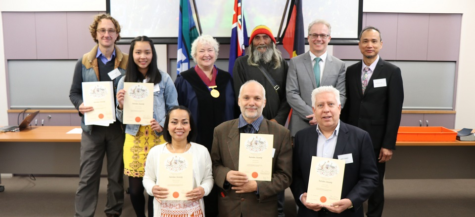Smiling new citizens with their citizenship certificates.