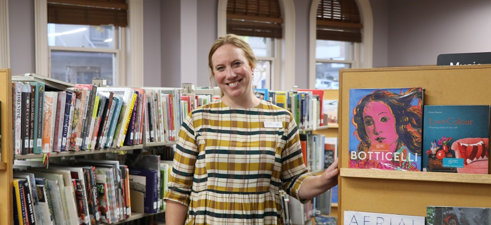 Jess standing in front of book shelves at the Castlemaine Library.