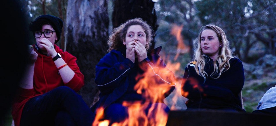 Young people outdoors around a fire.