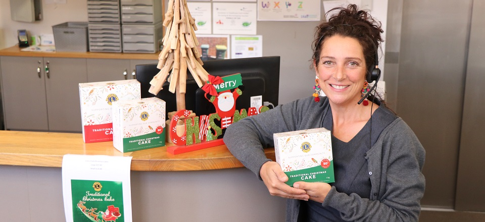 Customer Service staff member Nat with Lions Club Christmas cakes.