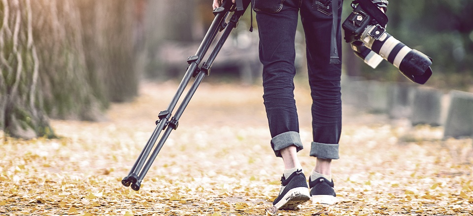 Person carrying a tripod and camera.