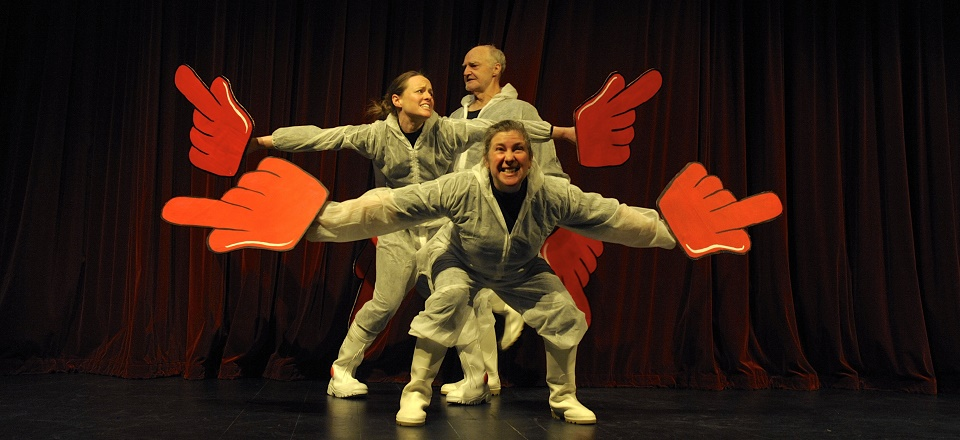 Three actors on stage with large red hand props.