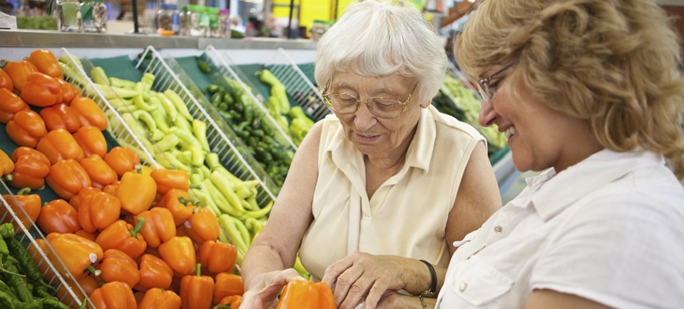 Image: Direct car worker assists an older client with shopping in the supermarket  Link to child page: In home support services