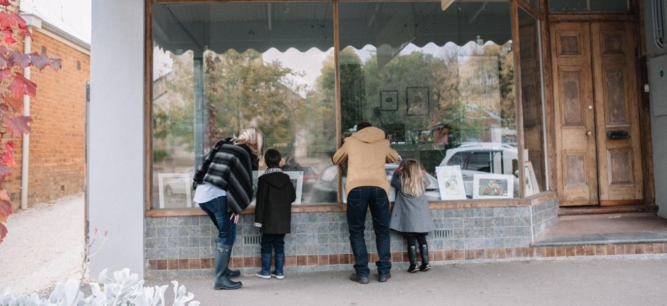 Image: A family admiring a historical shop front  Link to child page: Heritage projects & news