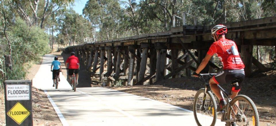 Riders cycle over the creek crossing along the Castlemaine to Maldon Trail