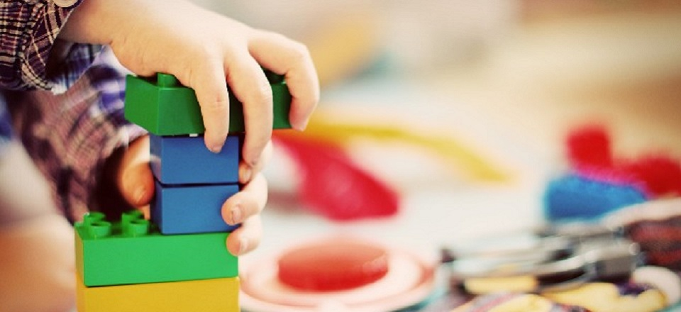 Child plays with colourful Duplo blocks