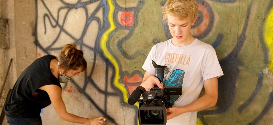 Teenage boy holds video camera