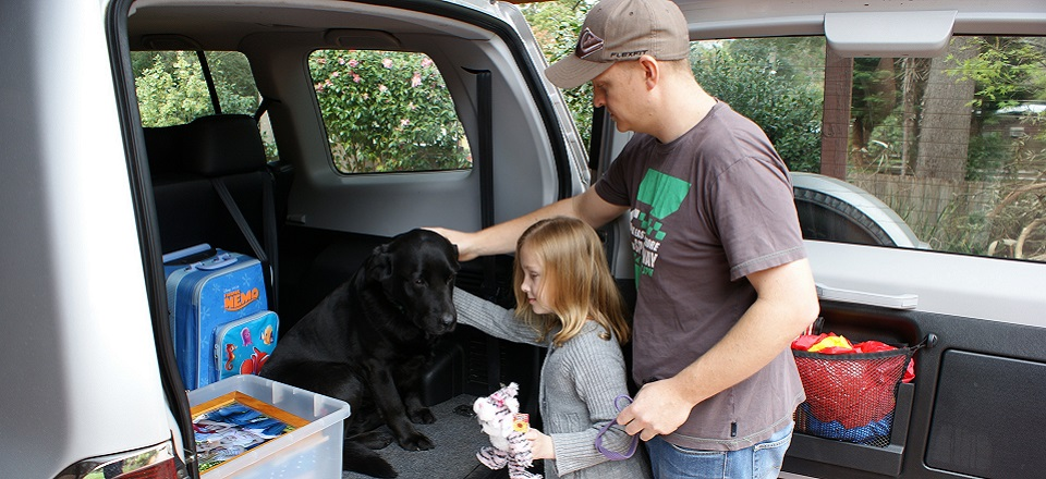 A child and adult pack their car including their black Labrador dog.