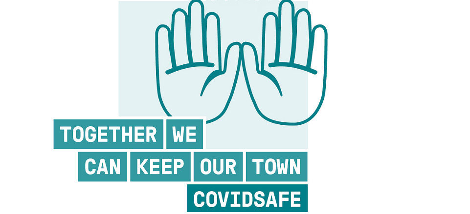 Two hands with COVIDSafe public health message - Together we can keep our town COVIDSafe