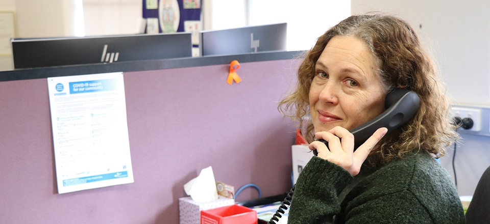 Image: Smiling Mel sitting at a desk holding a phone.  Link to child page: Community Activation and Social Isolation initiative (CASI)