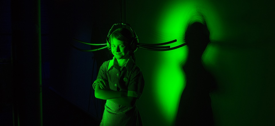 Smiling girl with large headphones in green light.