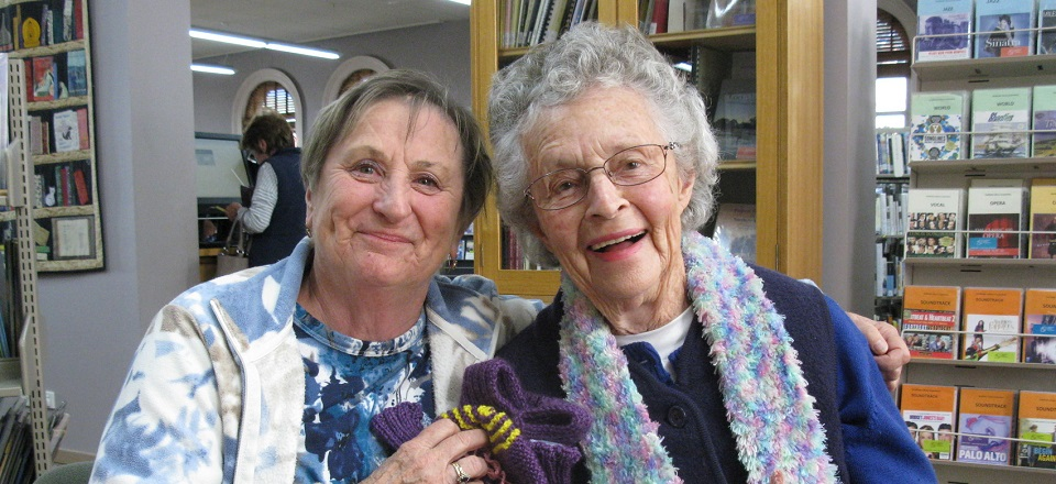 Image: Aileen and Norma with their knitting at the library  Link to child page: Seniors and carers