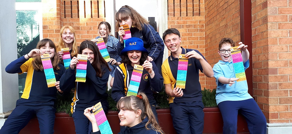 Smiling students with the colourful fold out Buzz It cards.